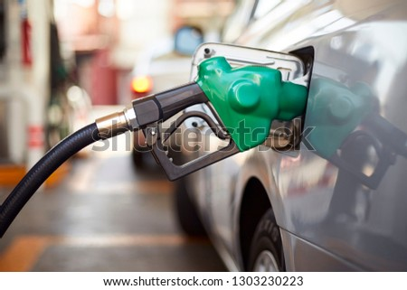 Fuel dispenser, hose and nozzle,refueling a car at the pump in a gas station, close up #1303230223
