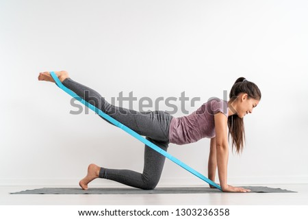 Resistance band fitness girl doing leg workout donkey kick floor exercises with rubber strap elastic. Glute muscle activation with kickback for cellulite. #1303236358