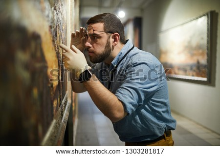 Side view waist up portrait of bearded museum worker inspecting painting for restoration, copy space