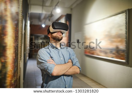 Waist up portrait of modern man wearing VR headset during virtual tour in art gallery or museum, copy space Royalty-Free Stock Photo #1303281820
