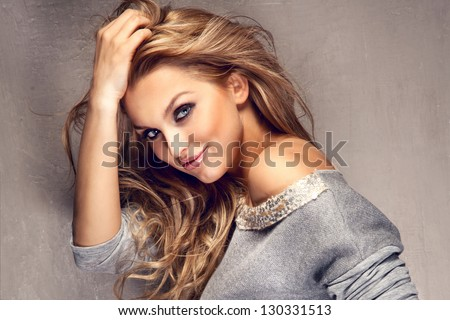 Portrait of wonderful young blonde woman with long hair looking at camera, smiling. #130331513