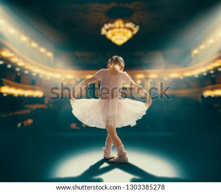 Cute little girl dreaming of becoming a ballerina. Child girl in a pink tutu dancing on the stage. Baby girl is studying ballet. #1303385278