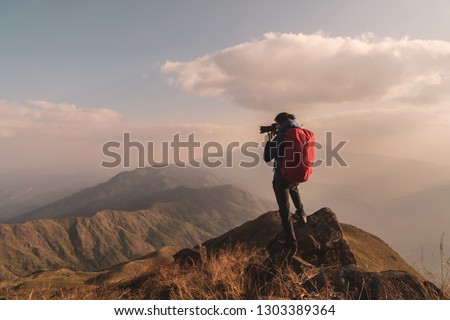 Young man traveler with backpack taking a photo on mountain, Adventure travel lifestyle concept