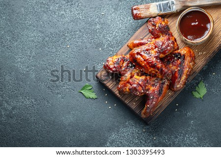 Roasted chicken wings in barbecue sauce with sesame seeds and parsley on a wooden board on a concrete table. Top view with copy space. Tasty snack for beer on a dark background. Flat lay #1303395493