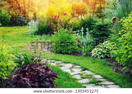 beautiful summer cottage garden view with stone pathway and blooming perennials #1303451275