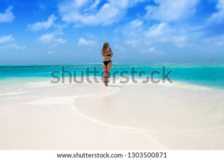 Blonde Girl in black bikini on dream beach at the turquoise ocean #1303500871