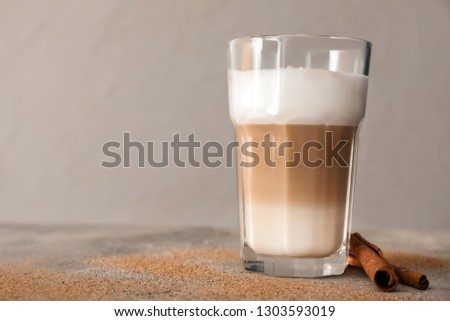 Glass of tasty aromatic latte on grey table #1303593019