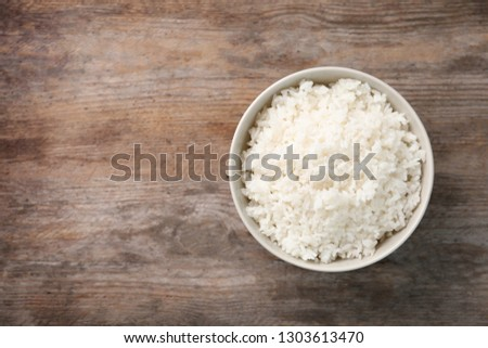 Bowl of boiled rice on wooden background, top view with space for text #1303613470