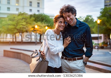 Romantic mature couple enjoying evening walk after office. Cheerful man and beautiful woman embracing while walking on city streets. Handsome man and woman spending evening together outdoors. #1303625386