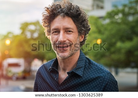 Portrait of happy mature man looking at camera outdoor. Senior businessman with beard feeling confident at sunset. Closeup face of business man smiling with city in background. #1303625389
