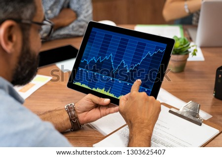 Mature latin businessman reading business graphs and stock charts on digital tablet. Rear view of business man holding tablet computer with stock analytics and abstract graphs. Close up hands working. #1303625407