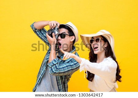 Amazed excited young Asian couple tourists in colorful yellow background