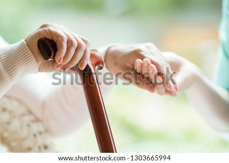 Closeup of elderly lady holding walking cane in one hand and holding volunteer's hand in the other #1303665994