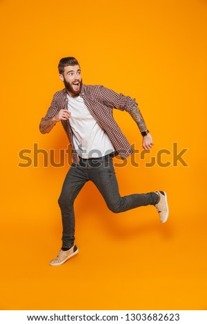 Full length portrait of a cheerful young man wearing casual clothes isolated over yellow background, running away #1303682623