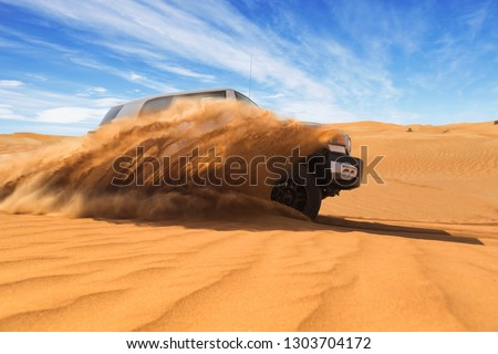 Drifting offroad car 4x4 in desert. Freeze motion of exploding sand powder into the air. Action and leasure activity. #1303704172