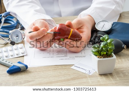 At doctors appointment physician shows to patient shape of liver with focus on hand with organ. Scene explaining patient causes and localization of diseases of liver, hepatobiliary system, gallbladder #1303725613
