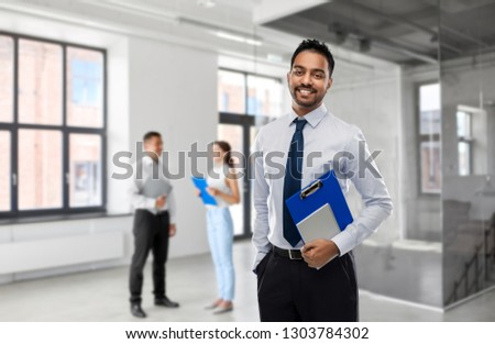 business, realty and people concept - smiling indian businessman or realtor with clipboard over empty office room background #1303784302