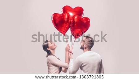 Valentine Couple. Portrait of Smiling Beauty Girl and her Handsome Boyfriend holding bunch of heart shaped air balloons and laughing. Happy Joyful Family. Love. Happy Valentine's Day #1303791805