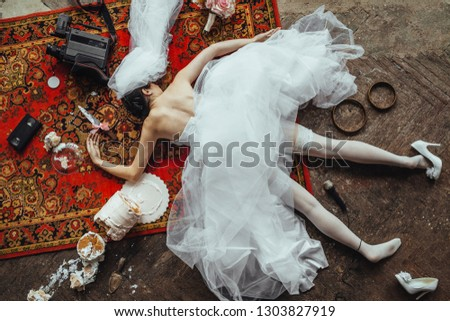 The bride fell into the wedding reception. The girl in the bride dress is lying face down on the floor. The accident at the wedding. Fun event at the wedding. Advertising of wedding clothes.  #1303827919