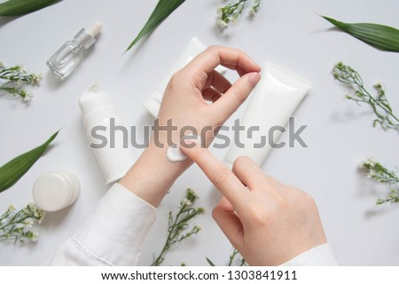 Scientist/Pharmacist applying moisturizer lotion on her hand for efficacy testing of natural organic skincare products in laboratory. Beauty cosmetic research and development concept. Top view. #1303841911