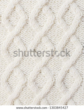 Sweater or scarf texture large knitting. Knitted jersey background with a relief pattern. Braids in knitting. Wool hand-knitted or machine knitting pattern. Fabric Background. #1303845427