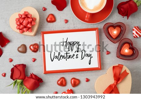 Valentine's day background with photo frame, coffee cup, heart shape chocolate, candles and gift boxes. Top view from above. Flat lay #1303943992