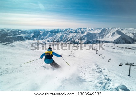 Male skier skiing on ski slope on a sunny winter day at the ski resort Gudauri in Georgia #1303946533