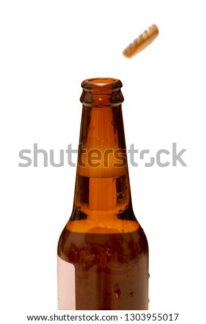 Cold beer opened bottle with popping caps on white background. Soda bottle. #1303955017