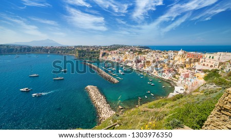 Colorful housing, fishing boats and yachts, cafes and restaurants in Marina Corricella, Procida island, Italy. Procida Island is located between Capo Miseno and Ischia island in Tyrrhenian sea. #1303976350