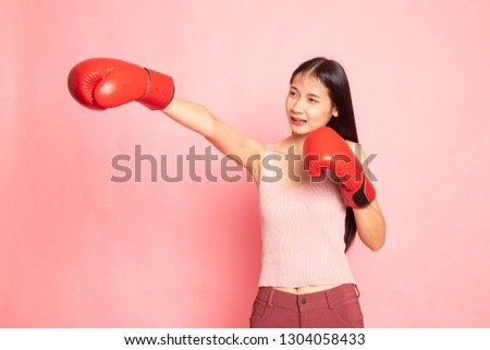 Young Asian woman with red boxing gloves on pink background #1304058433