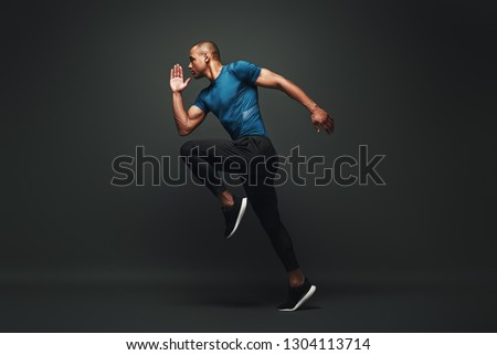 Deserve Victory. Sportsman jumping over dark background, he is ready to run Royalty-Free Stock Photo #1304113714
