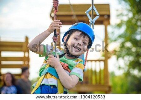 Young boy playing and having fun doing activities outdoors. Happiness and happy childhood concept. Boy swing on rope. #1304120533
