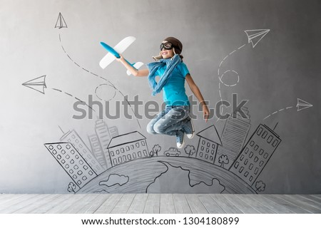 Happy child playing with toy airplane. Kid pilot ready to fly. Success, innovation and leader concept #1304180899