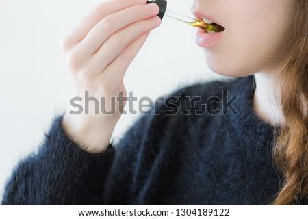 Woman Taking CBD Oil Under Tongue #1304189122