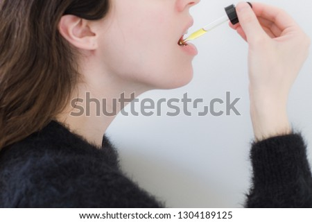 Woman Taking CBD Oil Under Tongue Royalty-Free Stock Photo #1304189125