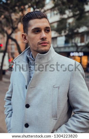 Close up of Portrait of businessman posing with gray raincoat in Barcelona city. Lifestyle #1304223820