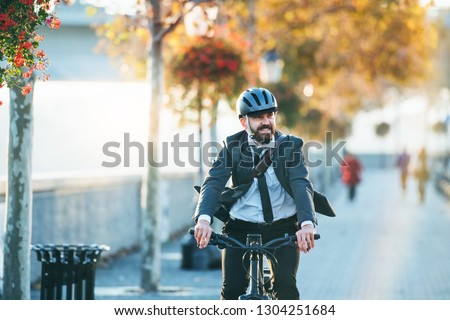 Hipster businessman commuter with electric bicycle traveling home from work in city. #1304251684