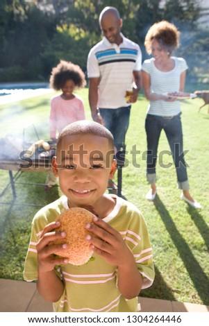 Boy eating burger family at barbeque in garden at camera #1304264446