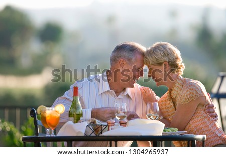 Loving mature couple eating at outdoor restaurant table #1304265937