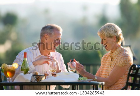 Mature man surprising woman with gift at outdoor restaurant table #1304265943