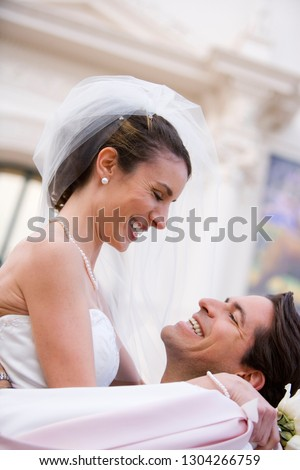 Loving bride and groom hugging outside church on wedding day #1304266759