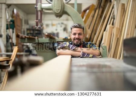 Portrait of professional woodworker standing next to a machine and wood material in his carpentry workshop. #1304277631