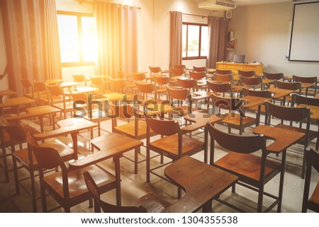 Empty school classroom with many wooden chairs. Wooden chairs in classroom. Wooden arranged in classroom. Empty classroom with vintage tone wooden chairs. Back to school concept. #1304355538