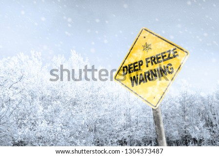 Winter season deep freeze polar vortex with snowflake symbol sign against a snowy background and copy space. Snow splattered and angled sign adds to the drama.