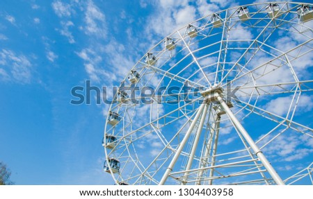 Ferris wheel an amusement-park or fairground ride consisting of a giant vertical revolving wheel with passenger cars suspended on its outer edge. #1304403958