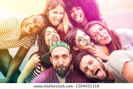 Multiracial millenial friends taking selfie with funny faces - Happy youth friendship concept against racism with international young trendy people having fun together - Psychedelic radial filter #1304431318