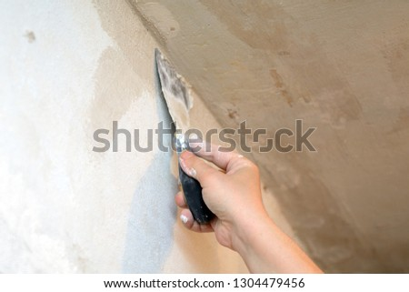male hand holding a trowel on weight closing up cracks in the ceiling #1304479456