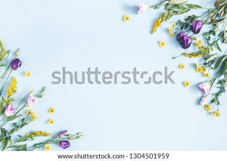 Flowers composition. Yellow and purple flowers on pastel blue background. Spring, easter concept. Flat lay, top view, copy space #1304501959
