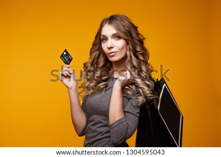 lose-up portrait of happy young brunette woman holding credit card and colorful shopping bags, looking at camera, isolated on yellow background #1304595043