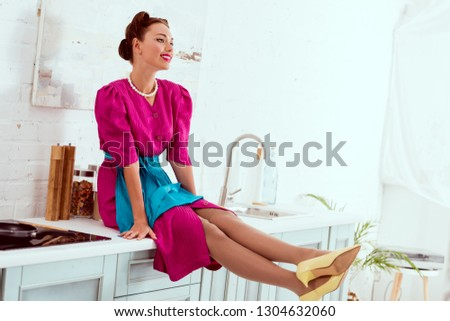Smiling pin up girl sitting on kitchen table with stretched legs #1304632060